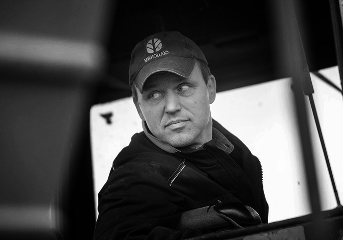 En svartvit bild av skribenten Mats Björklund i skärmmössa. Han sitter i en traktorhytt.