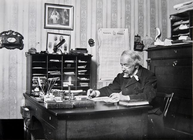 """Zacharias Topelius vid sitt arbetsbord i Björkudden i Sibbo år 1897. Bilden till höger visar utkastet till """"Giv mig ej glans, ej guld, ej prakt"""" som skrevs 1887."""