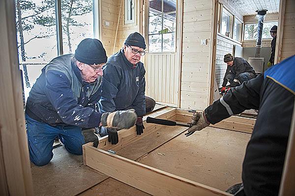 Christer Nyman och Leif Tallroth monterar ytterdörren medan Dag Granberg och Uno Höglund jobbar inne i själva bastun.