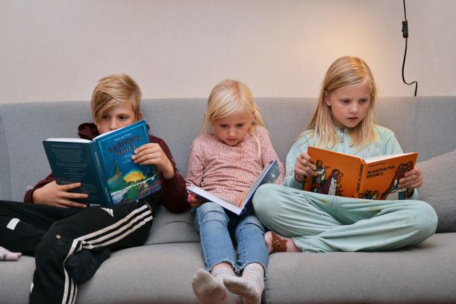 Silas, Nalani och Noomi Peltola läser ur olika barnbiblar som familjen har.