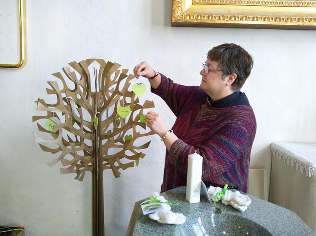 Tuija Wilman visar upp dopsymbolerna: dopträdet som står i kyrkan, ljuset och sockorna den nydöpta får som gåvor.