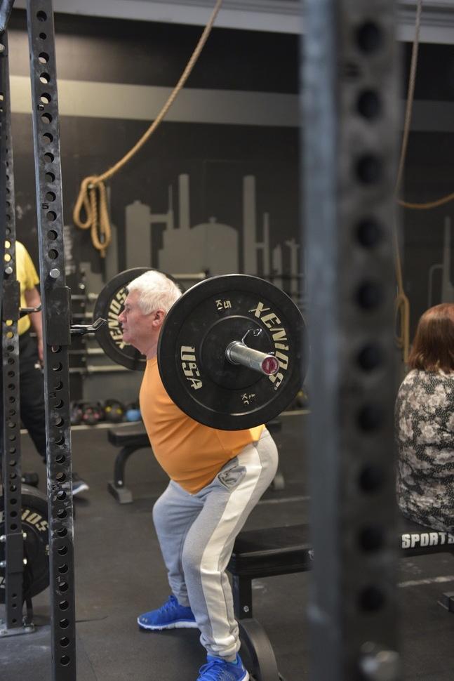 Dagens styrkeövning är knäböj. Ralf Bergholm har lastat vikter på skivstången.