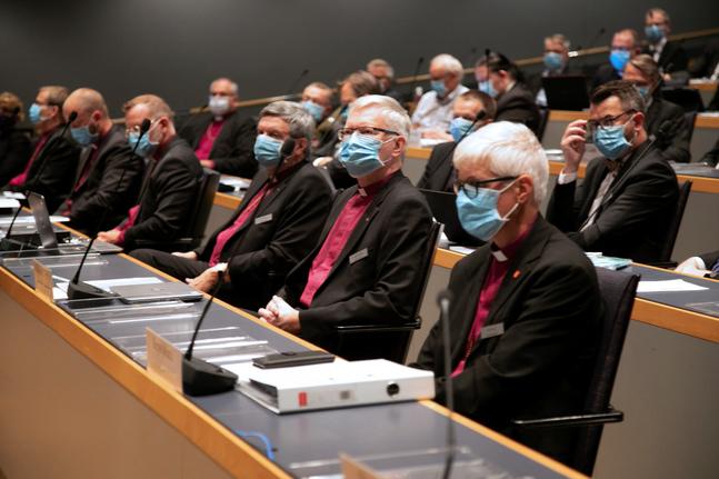 En annorlunda bild av kyrkomötet: ansikten bakom blå munskydd, talare med färggranna platshandskar och tekniska pauser för att desinficera mikrofoner.