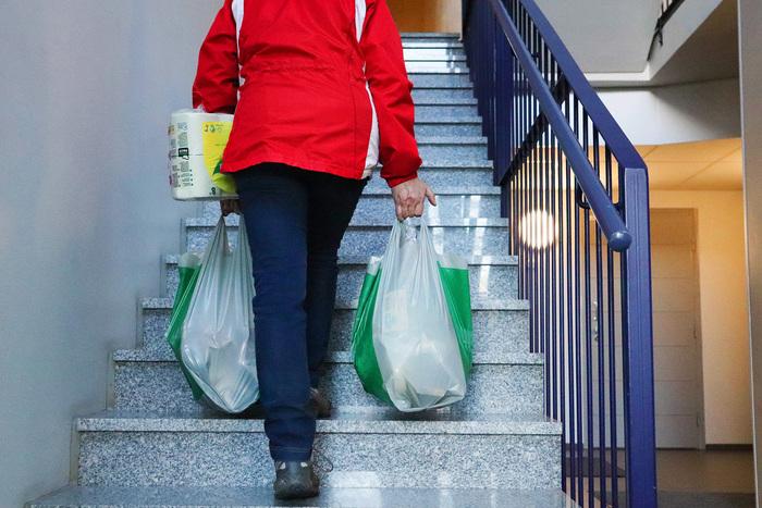 En person bär upp matkassar för trappan
